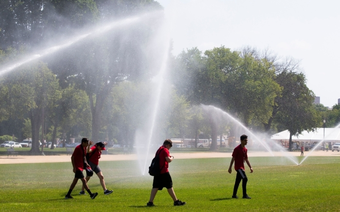 Youths walk under large sprinklers on the National Mall during an excessive heat watch in Washington, DC, USA, 19 July 2019. An excessive heat watch has been issued for the weekend in Washington DC. Meanwhile, a dangerous heat wave will cause close to 200 million people in the US to experience temperatures at 90 degrees Fahrenheit (32.22 Celsius) or higher this weekend, 19-21 July.Heat wave in Washington DC, USA - 17 Jul 2019