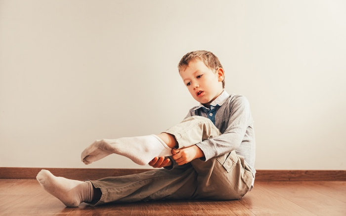 Child sitting on the floor putting on his socks with an expression of effort, concept of autonomy.; Shutterstock ID 1320557024; Usage (Print, Web, Both): Web; Issue Date: 8-29-19; Comments: For web story, best kids dress and trouser socks amazon