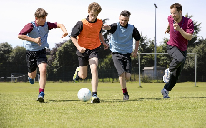 MINIMUM USAGE FEE £35. Please call Rex Features on 020 7278 7294 with any queriesMandatory Credit: Photo by Juice/Shutterstock (8787618a)MODEL RELEASED Middle schoolboys and teacher running playing soccer on field in physical education classVARIOUS