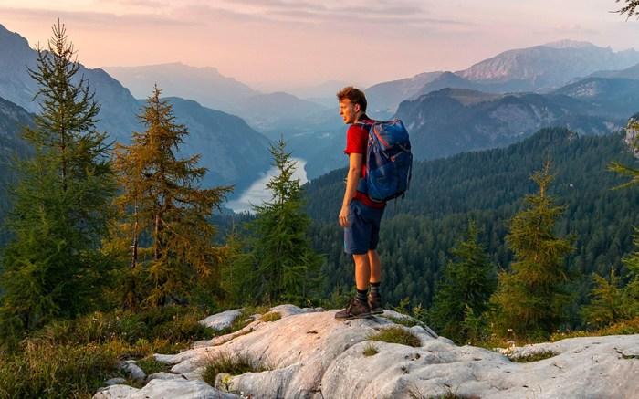 Hiker at the summit of Feldkogel, mountain landscape, view of Koenigssee at sunset, left Watzmann Suedspitze and Watzmannkinder, Berchtesgaden National Park, Berchtesgadener Land, Upper Bavaria, Bavaria, GermanyVARIOUS