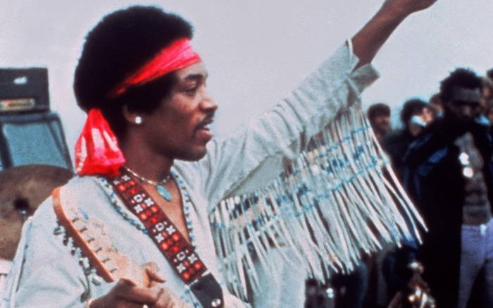 Jimi Hendrix onstage in a fringed jacket, turquoise jewelry and belt, bandana, Editorial use only. No book cover usage.Mandatory Credit: Photo by Warner Bros/Kobal/Shutterstock (5884678a)Jimi HendrixWoodstock - 1970Director: Michael WadleighWarner BrosUSAScene Still