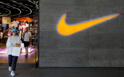 A woman walks past a logo