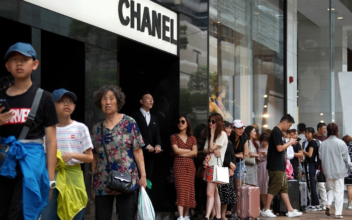 """Tourists, some with their luggage line up to get into the Chanel store at the Canton Road, the one-stop-shop high street of high-end brands and popular with mainland Chinese tourists in Hong Kong. It's still the world's """"freest"""" economy, one of the biggest global financial centers and a scenic haven for tycoons and tourists, but the waves of protests rocking Hong Kong are exposing strains unlikely to dissipate as communist-ruled Beijing's influence growsProtest Economy, Hong Kong, Hong Kong - 06 Jul 2019"""
