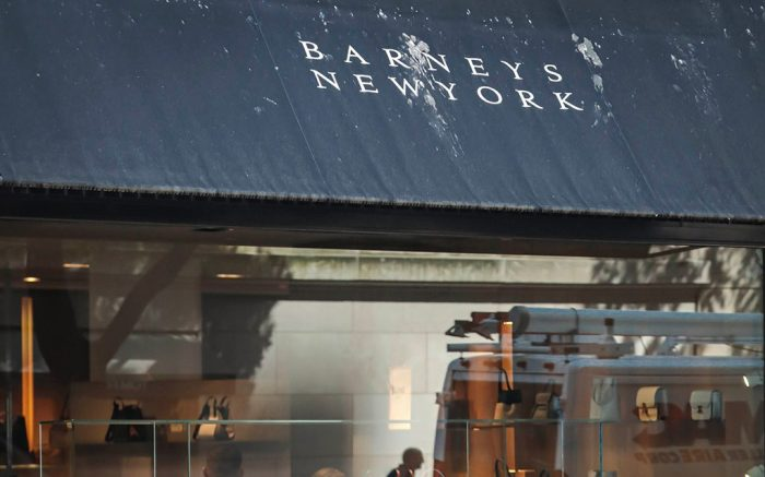 A pedestrian reflect in a store window at Barneys department store in New York. Barneys New York, which opened its 10-story Madison Avenue store in 1993, became a cultural icon in luxury shopping but now risks closure. High rents and a dramatic shift toward online shopping are pressuring it to evaluate restructuring options, including possible bankruptcy, according to a source close to the matter who asked to remain anonymous because the discussions are confidentialReimagining Flagship Stores, New York, USA - 15 Jul 2019
