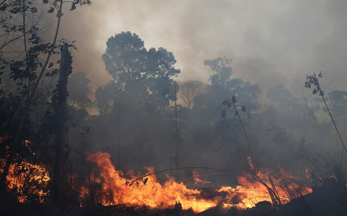"""A fire burns along the road to Jacunda National Forest, near the city of Porto Velho in the Vila Nova Samuel region which is part of Brazil's Amazon, . The Group of Seven nations on Monday pledged tens of millions of dollars to help Amazon countries fight raging wildfires, even as Brazilian President Jair Bolsonaro accused rich countries of treating the region like a """"colonyAmazon Fires, Porto Velho, Brazil - 26 Aug 2019"""