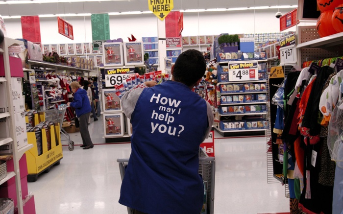 'How may I help you?' on uniform worn by shop worker, Walmart superstore, New York, AmericaAMERICA - 2004