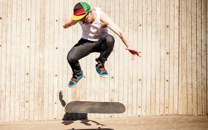 MODEL RELEASED Caucasian man doing skate trick near wooden wallVARIOUS