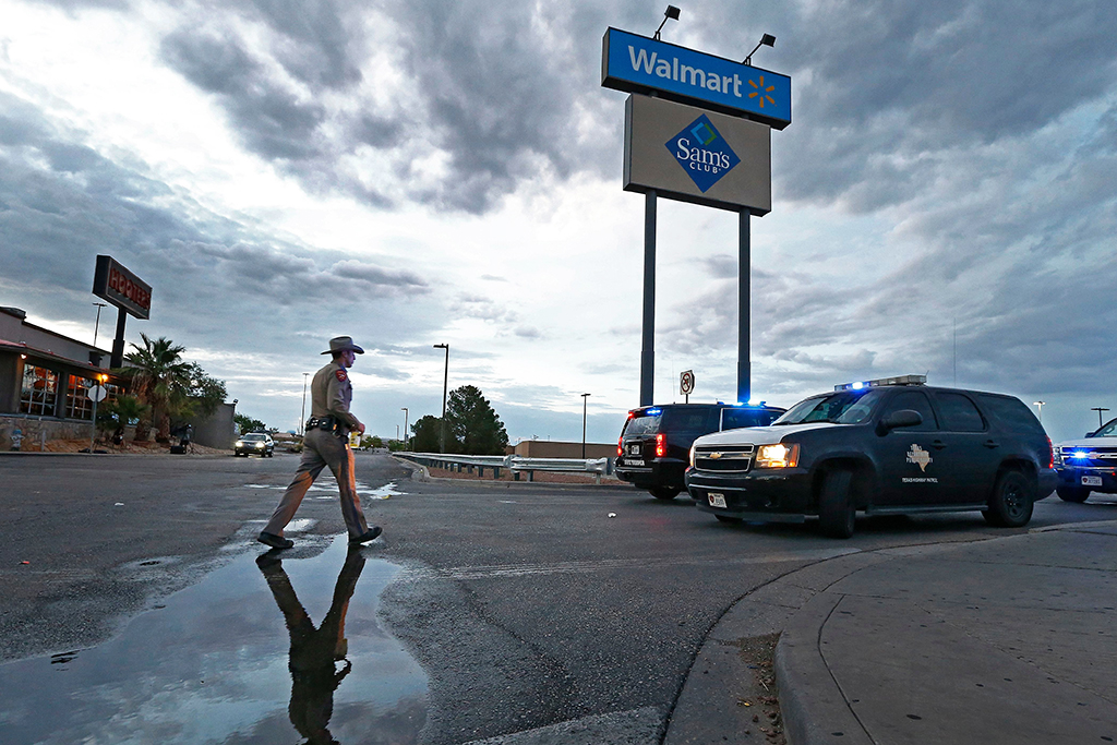 A Texas State Trooper walks in front of a Walmart sign