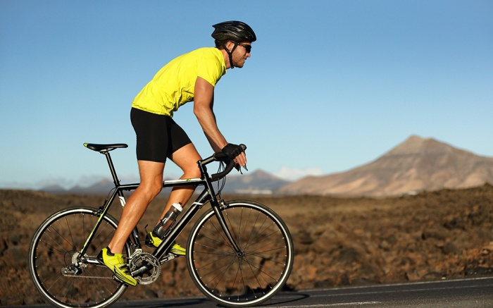 Biking cyclist male athlete going uphill on open road training hard on bicycle outdoors at sunset. Nature landscape.; Shutterstock ID 1008439891; Usage (Print, Web, Both): web; Issue Date: 9/27
