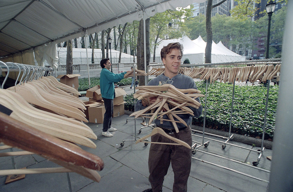 Michael McArdle, right, juggles an armful of coat hangers as he puts them on racks in New York City?s Bryant Park on in preparation for next week?s ?Seventh on Sixth? spring fashion shows. The shows will be held for the first time under two tents and inside the main branch of the public library adjacent to the parkTents Bryant Park Manhattan Fashion, New York, USA, nyfw history