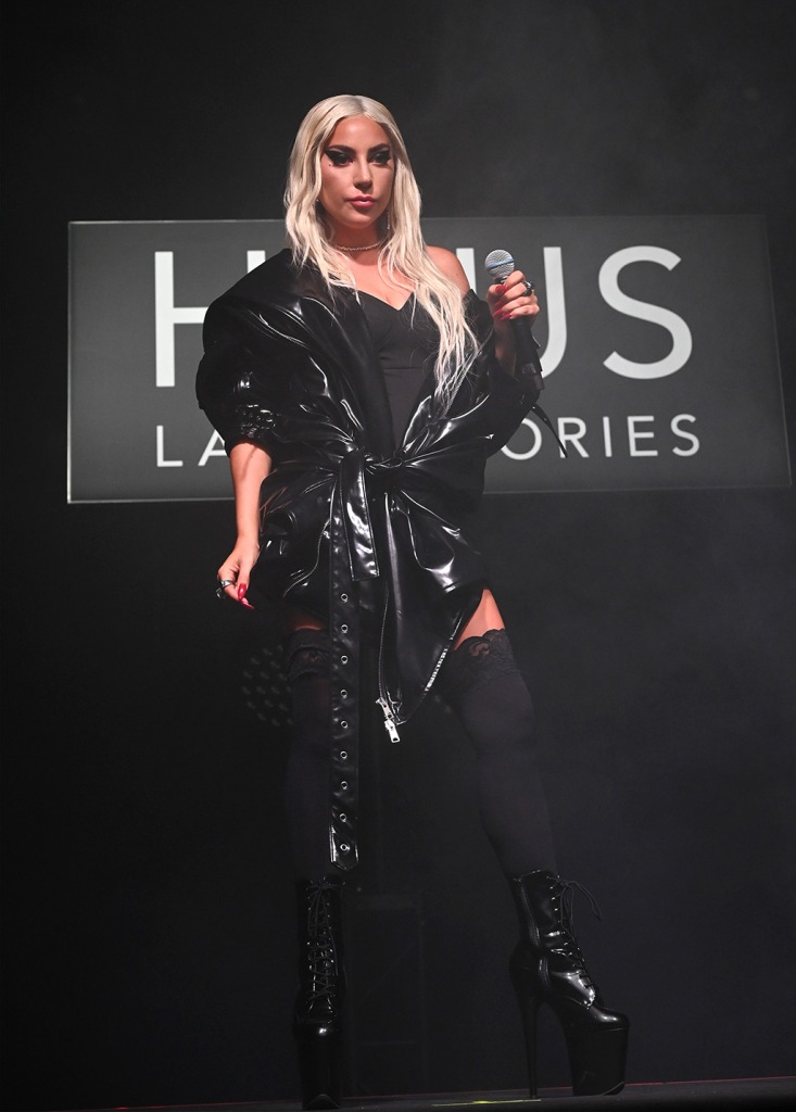 Lady Gaga, pvc coat, Kaiman, celebrity style, pleaser shoes, platform shoes, SANTA MONICA, CALIFORNIA - SEPTEMBER 16: Lady Gaga speaks onstage during Lady Gaga Celebrates the Launch of Haus Laboratories at Barker Hangar on September 16, 2019 in Santa Monica, California. (Photo by Kevin Mazur/Getty Images for Haus Laboratories)