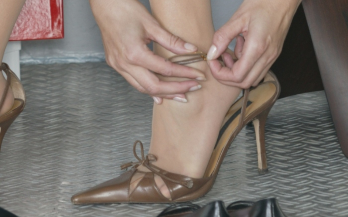 woman putting on shoe