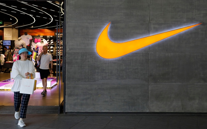 A woman walks past a logo of Nike outside Nike store in Beijing, China