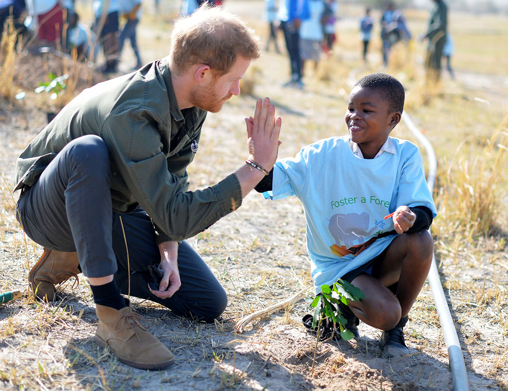 Britain's Prince Harry, Duke of Sussex (L) gives a high five to a child as he joins school children in a tree planting event in Chobe National Park, Kasane, Botswana, 26 September 2019. Chobe National Park is home to Africa?s largest elephant population (more than 17,000) and comprises more than 10,000 km2 of rich ecosystems, diverse landscapes and an abundance of wildlife and birdlife who depend on the Chobe River as a critical source of water. The Duke and Duchess of Sussex are on an official visit to Africa.Duke and Duchess of Sussex on royal tour of Africa, Kasane, Botswana - 26 Sep 2019