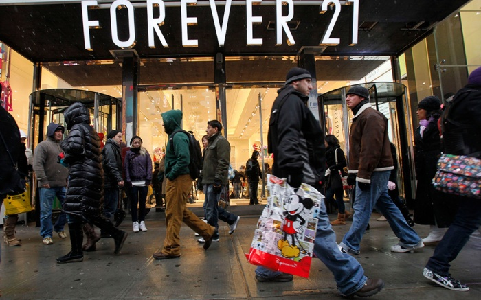 People walk past a Forever 21 store in New York's Times Square. The population of the U.S. has grown by 8 million people since the previous record was set. That means there were millions more shoppers in stores this Christmas, driving up the sales total. But the average amount of spending per person was down from a few years ago, suggesting consumers are still slower to pull out their walletsHoliday Record, New York, USA