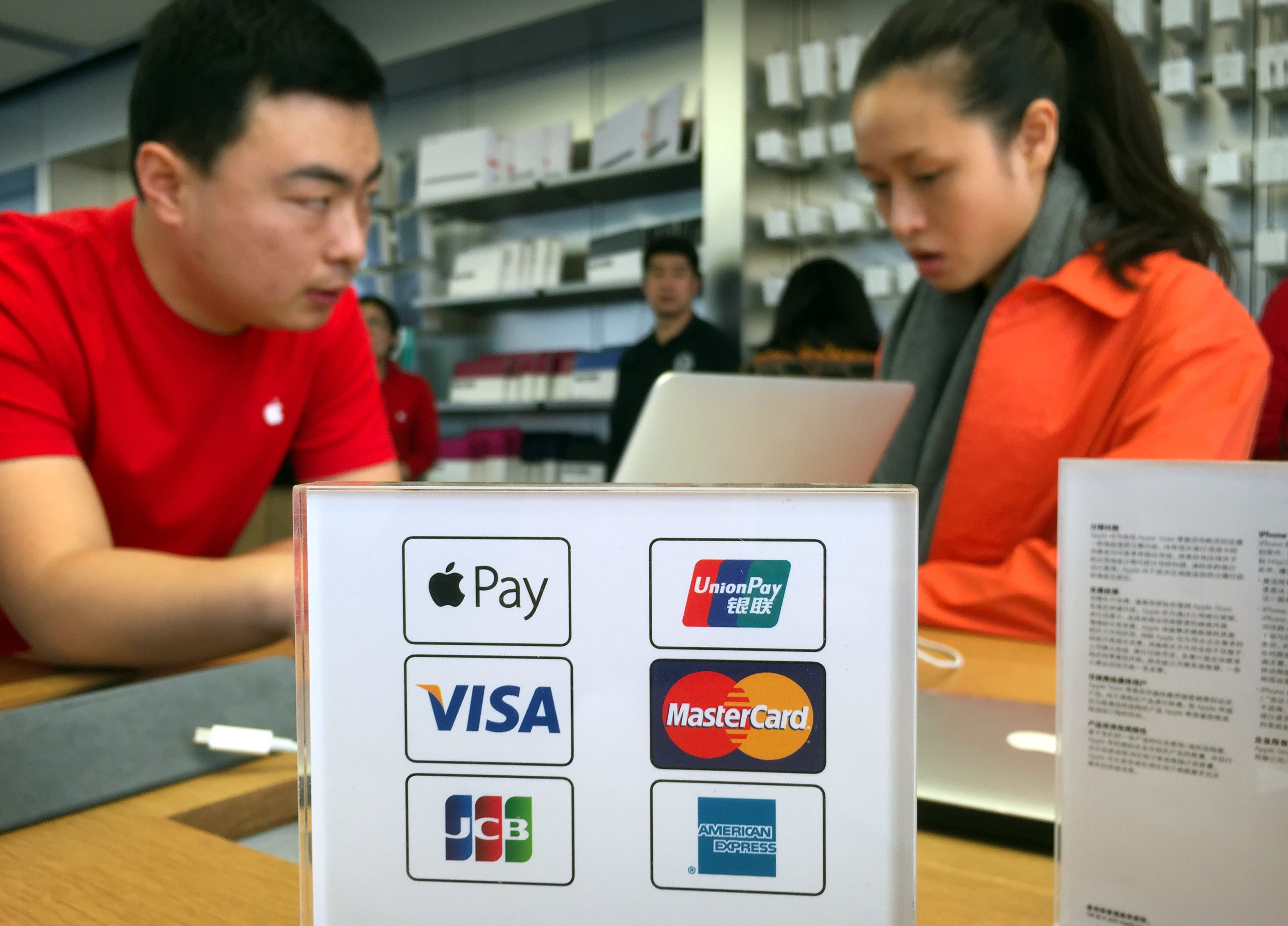 An employee works on a laptop computer as he talks with a customer near a sheet showing accepted methods of payment, including Apple Pay, top left, at an Apple Store in Beijing, . Apple Inc. on Thursday launched its smartphone-based payment system in China where the electronic payments market is already dominated by an arm of e-commerce giant AlibabaChina Apple Pay, Beijing, China
