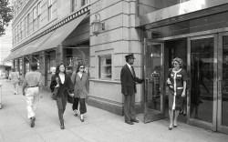 Pedestrians walk past the Barney's store