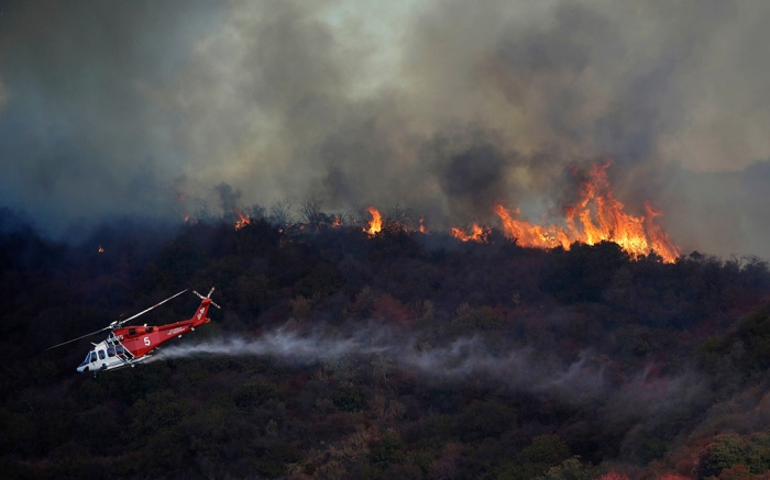 A wildfire called the Getty Fire burns a ridge top as a water-dropping helicopter flies by on Mandeville Canyon, in Los AngelesCalifornia Wildfires Blackout, Los Angeles, USA - 28 Oct 2019