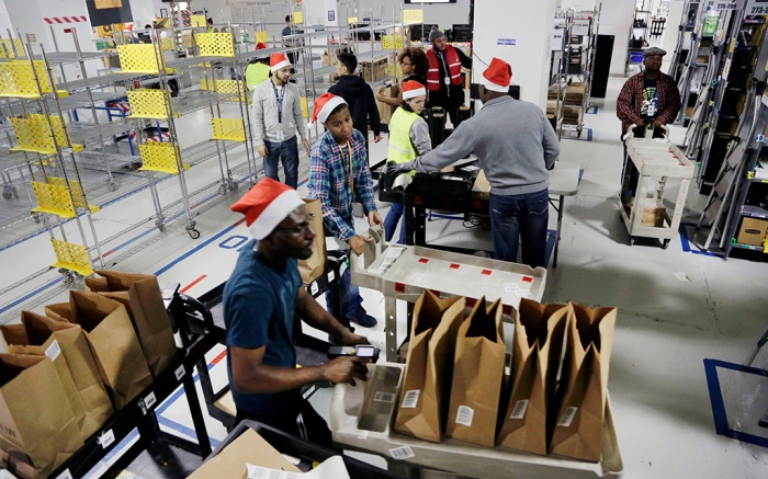 Amazon Prime employees push carts with bags loaded with goods for delivery to customers at the company's urban fulfillment facility, in New York. This holiday season, Amazon Prime customers, using the Amazon Prime Now app, can choose from thousands of items including gifts, pantry items, and electronics and get free delivery in less than two hours through Christmas EveAmazon Prime, New York, USA