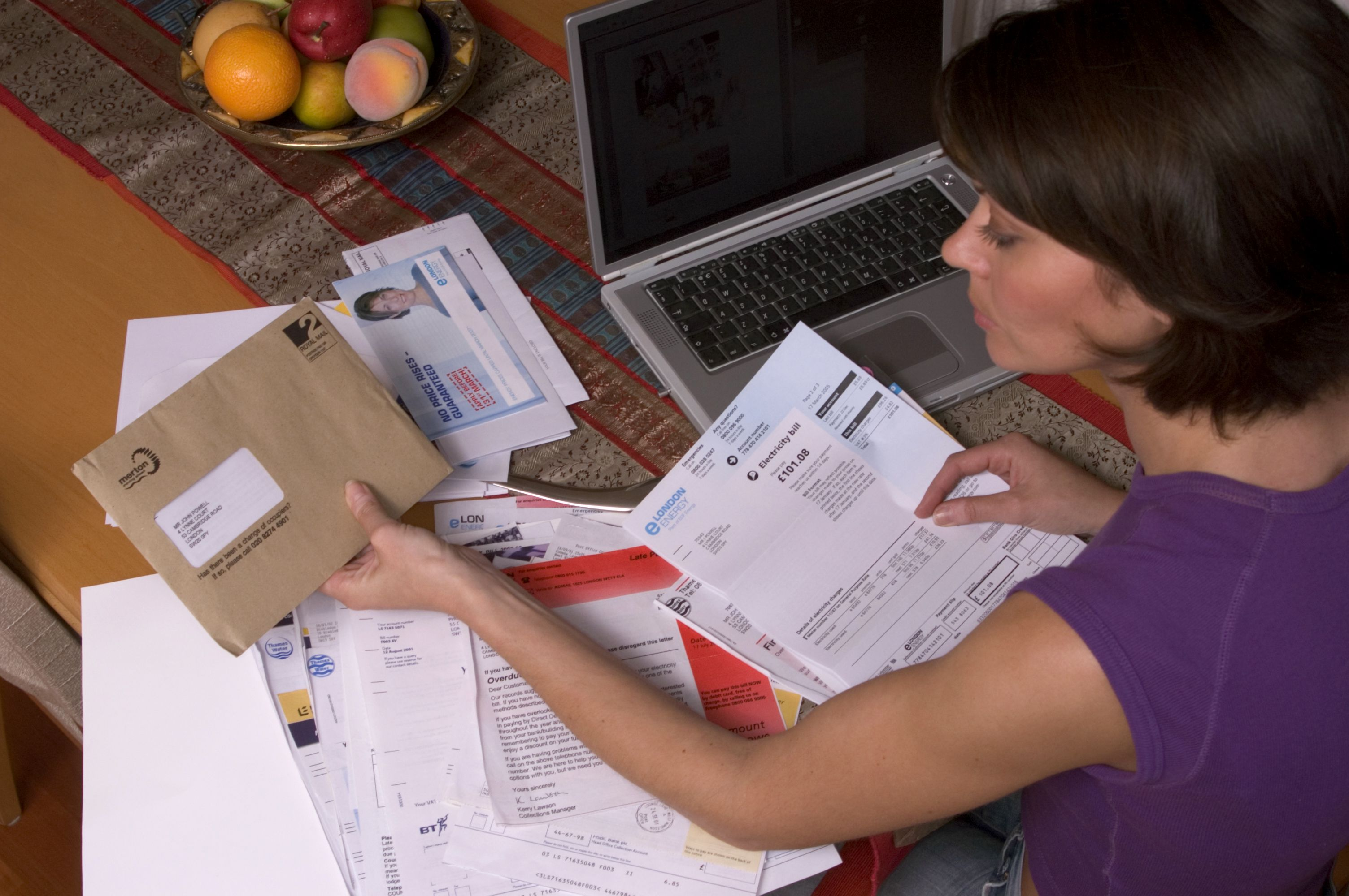 MODEL RELEASED - WOMAN SORTING HER PAPERWORK NEXT TO A LAPTOP COMPUTERVARIOUS