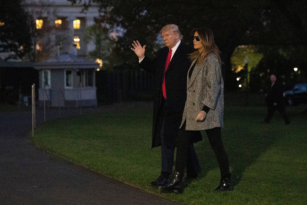 Melania Trump, black and white coat, red valentino coat, skinny jeans, black pants, combat boots, new york city, air force one, november 2019, Donald Trump, Melania Trump. President Donald Trump and first lady Melania Trump walk on the South Lawn of the White House in Washington, after stepping off Marine One as they return from New YorkTrump, Washington, USA - 12 Nov 2019