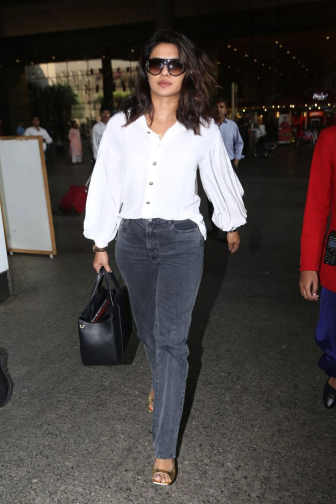 priyanka chopra, white blouse, gray jeans, gold sandals, square toes, sunglasses, black handbag, airport, mumbai,