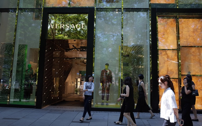 People walk pass by a Versace store in a commercial district in Beijing, China, 13 August 2019. Fashion brands Versace and Coach apologize to Chinese customers after social media users called for a boycott of the brands due to separate T-shirts from both fashion houses that suggested Hong Kong and Taipei were separate from China. And also Swarovski apologizes to Chinese customers for erroneously describing Hong Kong as a country on its website.Fashion brands apologize to China over t-shirt, Beijing - 13 Aug 2019