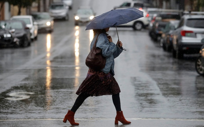 A woman carries an umbrella while walking in the rain in San Francisco, . Northern California and southern Oregon residents are bracing for a 'bomb cyclone' that's expected at one of the busiest travel times of the yearWinter Weather Travel, San Francisco, USA - 26 Nov 2019