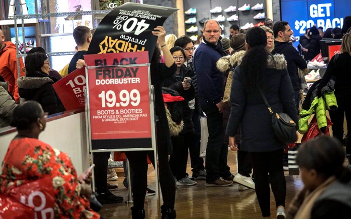 An employee posts discount signs for shoppers at Macy's department store during Black Friday shopping, in New York. Black Friday shoppers fought for parking spots and traveled cross-state to their favorite malls, kicking off a shortened shopping season that intensified the mad scramble between Thanksgiving and ChristmasBlack Friday Shopping, New York, USA - 29 Nov 2019