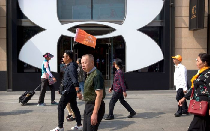 """A Chinese tour guide leads a tour group past a store from American sportswear retailer Under Armour at an outdoor shopping area in Beijing, . A Chinese trade envoy said Tuesday that talks with Washington are impossible while the United States """"holds a knife"""" to Beijing's neck by imposing tariff hikesUS Tariffs, Beijing, China - 25 Sep 2018"""