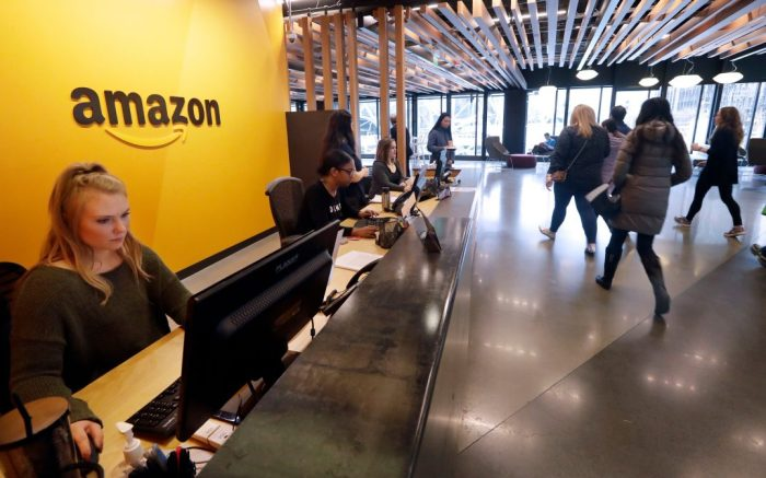 Employees walk through a lobby at Amazon's headquarters, in Seattle. Amazon, which is growing too big for its Seattle hometown, is spreading out to the East Coast. The online shopping giant ended its 14-month-long competition for a second headquarters Tuesday by selecting New York and Arlington, Va., as the joint winnersAmazon HQ, Seattle, USA - 13 Nov 2018