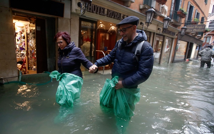 A couple wades their way through water in Venice, Italy, . Waters are rising in Venice where the tide is reaching exceptional levels just three days after the Italian lagoon city experienced its worst flooding in more than 50 yearsFlooding, Venice, Italy - 15 Nov 2019