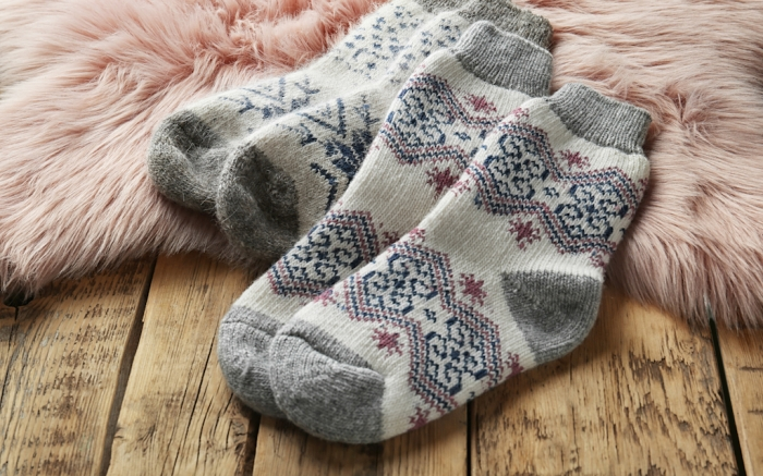 Knitted socks and pink faux fur on wooden table, closeup; Shutterstock ID 1536206612; Usage (Print, Web, Both): web; Issue Date: 11/22