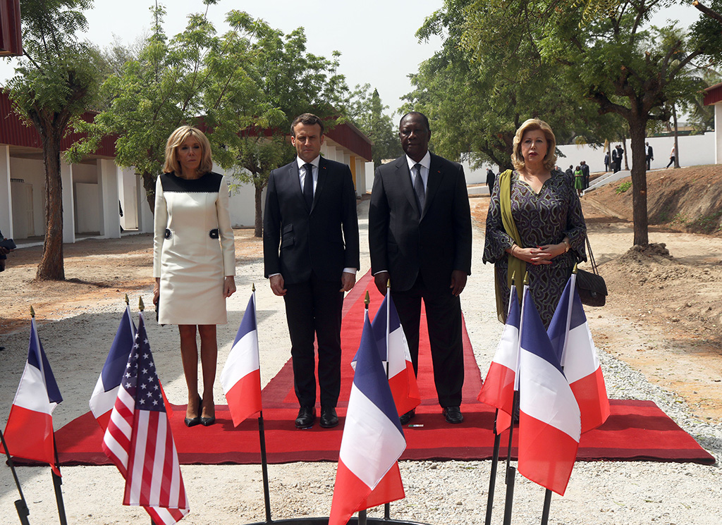 brigitte macron, black and white dress, black pumps, French President Emmanuel Macron (2-L) and his wife Brigitte Macron (L) with Ivory Coast President Alassane Ouattara (2-R) and his wife Dominique (R) pay homage to the French and U.S. soldiers killed in 2004, as they visit the city of Bouake, Ivory Coast, 22 December 2019. President Macron began his official three-day visit to Ivory Coast where he meets with president President of Ivory Coast Alassane Ouattara, before visiting Niger. The visit is expected to bolster economic ties with the former colony as well as focus on security issues within the region.French President Emmanuell Macron visits Ivory Coast, Bouake - 22 Dec 2019