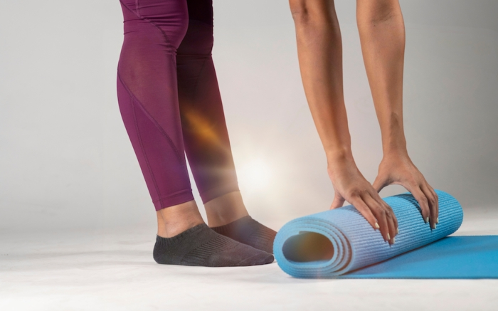 Close-up view of  female hands and feet wearing black socks rolling up a blue yoga mat on a light gray background; Shutterstock ID 1230244669; Usage (Print, Web, Both): web; Issue Date: 11/22