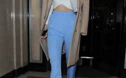 Kendall Jenner leaving Claridge's Hotel in Mayfair, wearing blue trousers, a white top that exposed her toned stomach, and a tan coloured coat