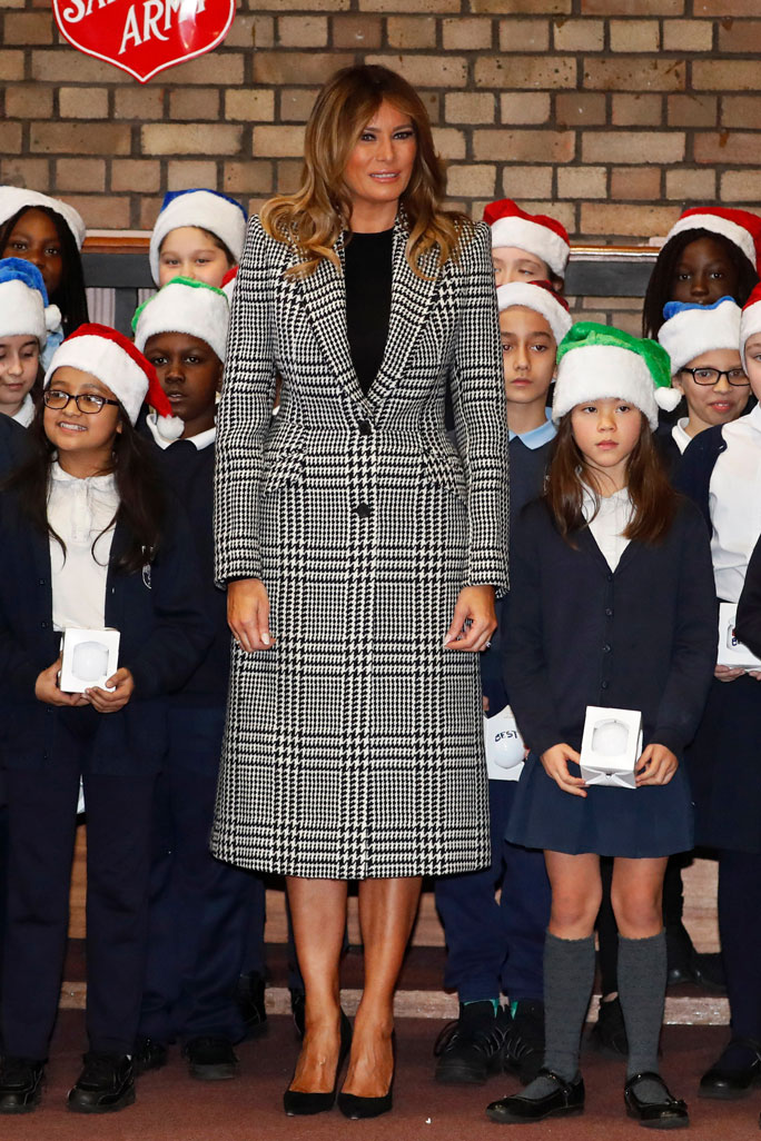 melania trump, celebrity style, black and white outfit, houndstooth coat dress, black dress, stilettos, power pumps, First lady, Melania Trump poses with a children choir after joining local students and U.S. Marines stationed at the U.S. Embassy, wrapping holiday presents to be donated to the Salvation Army, at the Salvation Army Clapton Center in LondonMelania Trump, London, United Kingdom - 04 Dec 2019