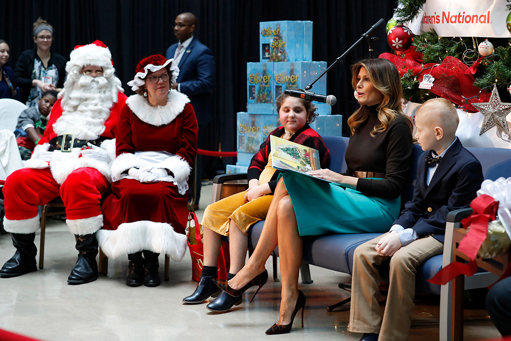Melania Trump, prada skirt, turquoise skirt, christian louboutin shoes, stilettos, leopard print shoes, Sammie Burley, Declan McCahan. First lady Melania Trump reads a Christmas book to children as she is seated between patients at Children's National Hospital, Sammie Burley, left, and Declan McCahan, right, in WashingtonMelania Trump, Washington, USA - 05 Dec 2019