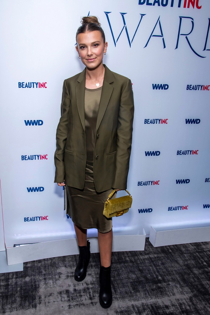 Millie Bobby Brown, red carpet, celebrity style, olive green dress, blazer, black boots, ankle boots, attends the WWD Beauty Inc Awards at the Rainbow Room, in New York2019 WWD Beauty Inc Awards, New York, USA - 11 Dec 2019