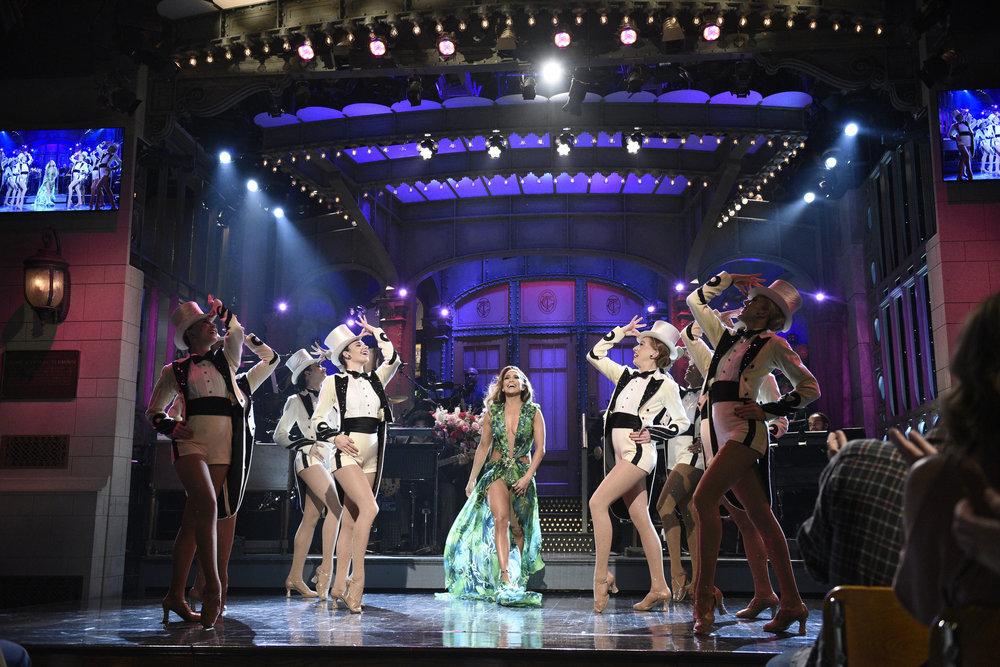 "SATURDAY NIGHT LIVE, jlo, jennifer lopez, versace dress, radio city rockettes, -- ""Jennifer Lopez"" Episode 1775 -- Pictured: Host Jennifer Lopez with The Rockettes during the Monologue on Saturday, December 7, 2019 -- (Photo by: Will Heath/NBC)"