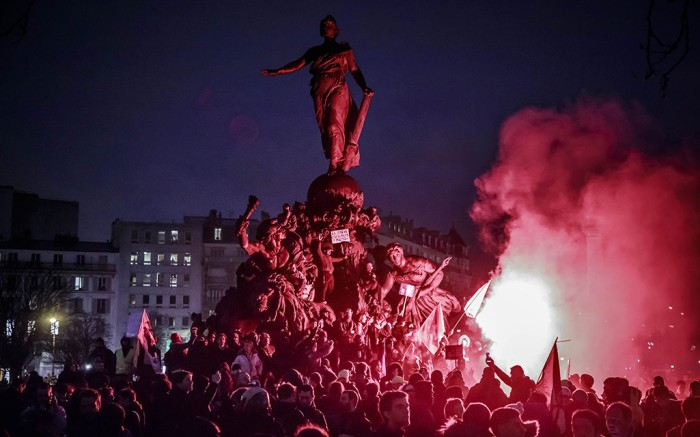 Pension reform protesters scale a statue in Paris' Place de la République.