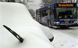 Snow covers parked vehicles after an