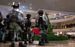 Riot police stand guard during a