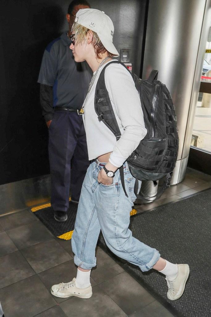 Kristen Stewart, converse jack purcell, white sneakers, boyfriend jeans, crop top, sunglasses, nike backpack, backward baseball cap, Kristen Stewart at LAX International Airport, Los Angeles, USA - 08 Jan 2020