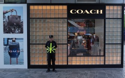 A public security stands outside a