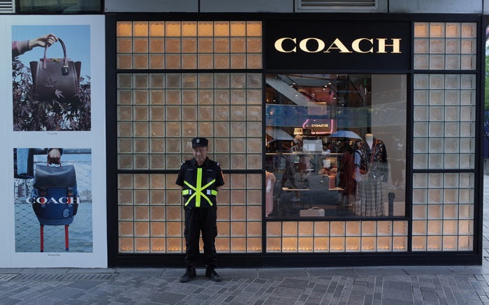 A public security stands outside a Coach store in a commercial district in Beijing, China, 13 August 2019. Fashion brands Versace and Coach apologize to Chinese customers after social media users called for a boycott of the brands due to separate T-shirts from both fashion houses that suggested Hong Kong and Taipei were separate from China. And also Swarovski apologizes to Chinese customers for erroneously describing Hong Kong as a country on its website.Fashion brands apologize to China over t-shirt, Beijing - 13 Aug 2019