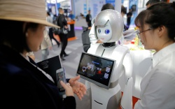 A visitor looks at a robot