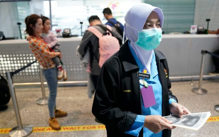 A health official hands out information about the current coronavirus at the Kuala Lumpur International Airport in Sepang, Malaysia, . Countries both in the Asia-Pacific and elsewhere have initiated body temperature checks at airports, railway stations and along highways in hopes of catching those at risk of carrying a new coronavirus that has sickened more than 200 people in ChinaChina Outbreak, Sepang, Malaysia - 21 Jan 2020