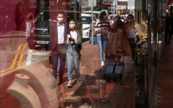 Pedestrians cover their faces with sanitary