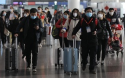 Passengers wearing masks are seen at